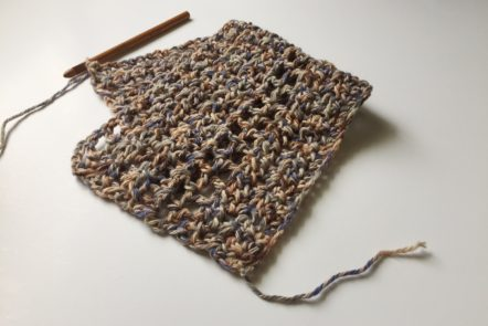 Crochet sample with neutral yarn and wooden hook.