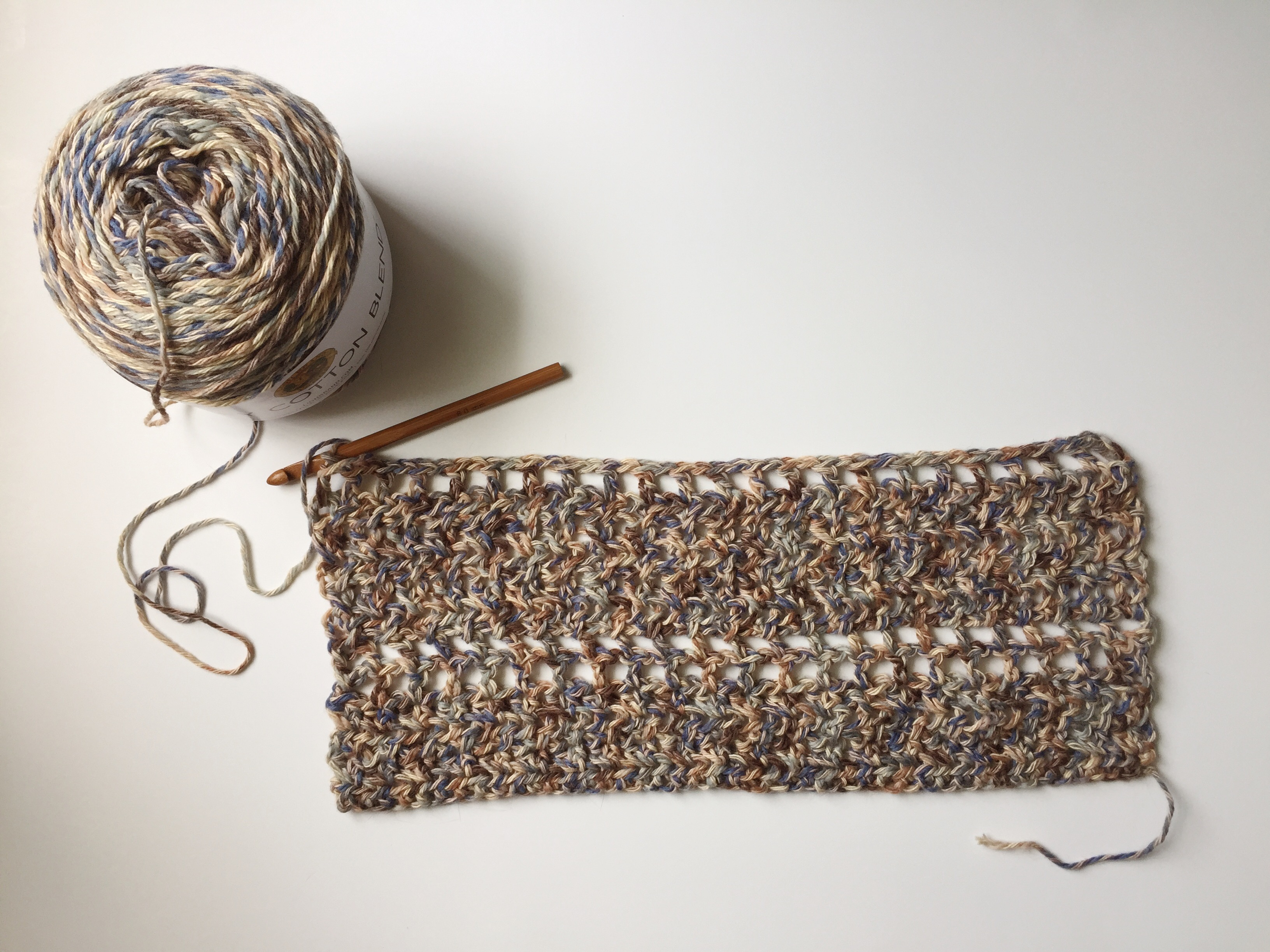 The start of a crochet shawl with neutral cotton yarn and a wooden crochet hook.